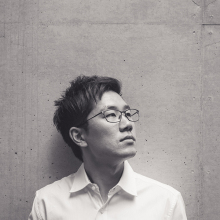 Black & white photo of Sun-ha looking off to his left and slightly up, wearing glasses and w white collared shirt. He has black hair. His head is centered in the frame and he's standing up against a wall. The photo starts about one foot above his head and ends just above his chest.
